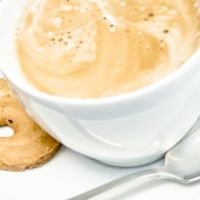 Kaffeetasse mit Löffel und Gebäck