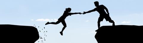 Mann reicht springender Frau die Hand.